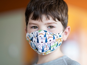 Young boy wearing a mask.