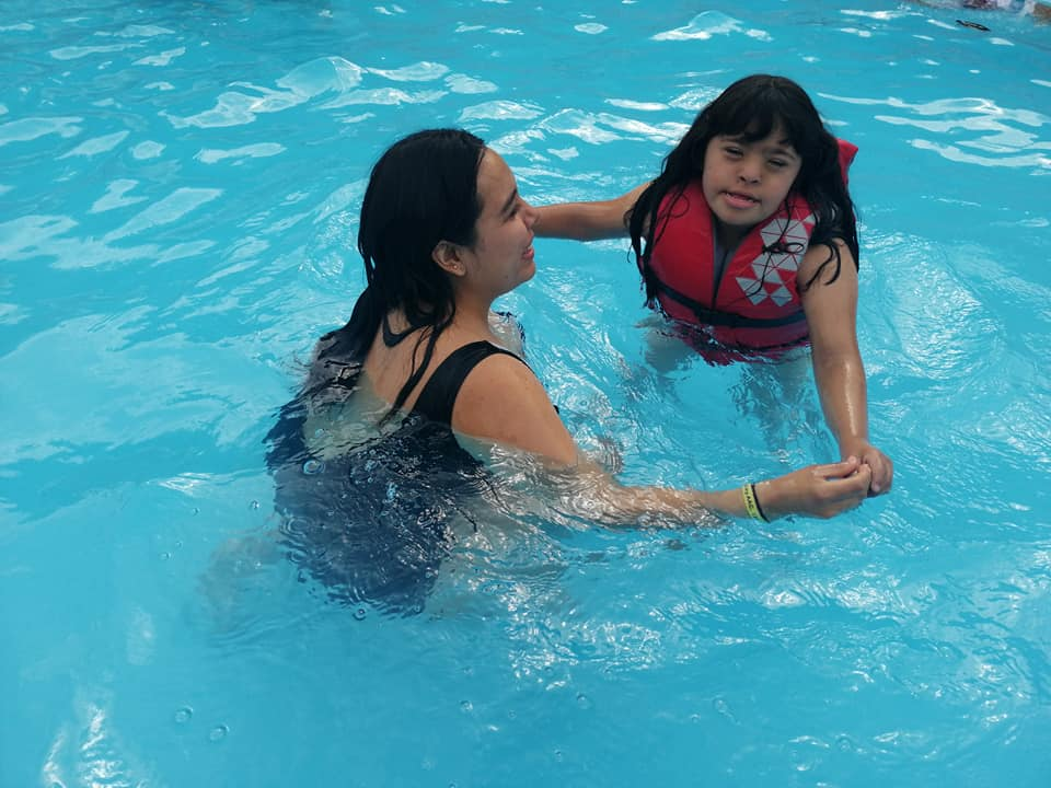 A camper and her counselor swim in the heated pool.