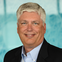 Headshot photograph of Dana Moore, vice president and CIO of Children's Hospital Colorado. He has short salt and pepper hair and is wearing a black suit jacket.