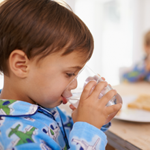 A young child with short brown hair is drinking a glass of water at the breakfast table as a healthy alternative to sugar sweetened beverages like juice.