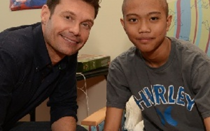Ryan Seacrest poses for a picture with a boy at Children's Colorado.