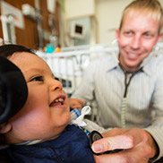 A doctor with blond hair and a white striped shirt listens to a young boy's heart through a stethoscope.