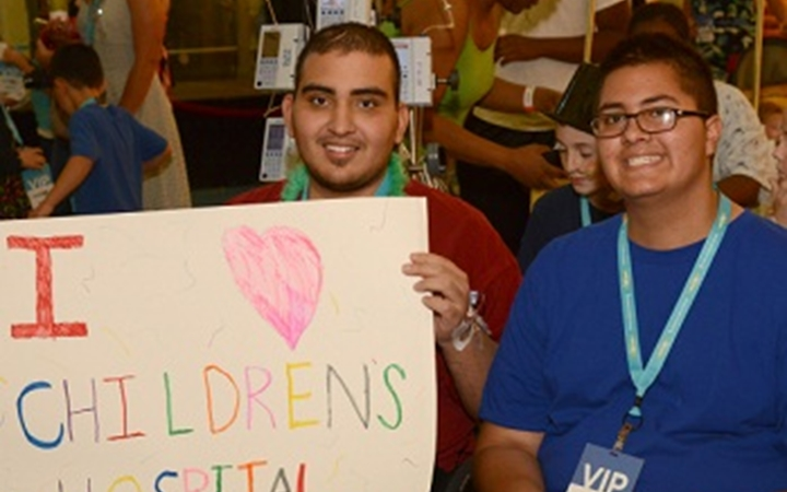 A teenager holds a sign that says I love Children's Hospital