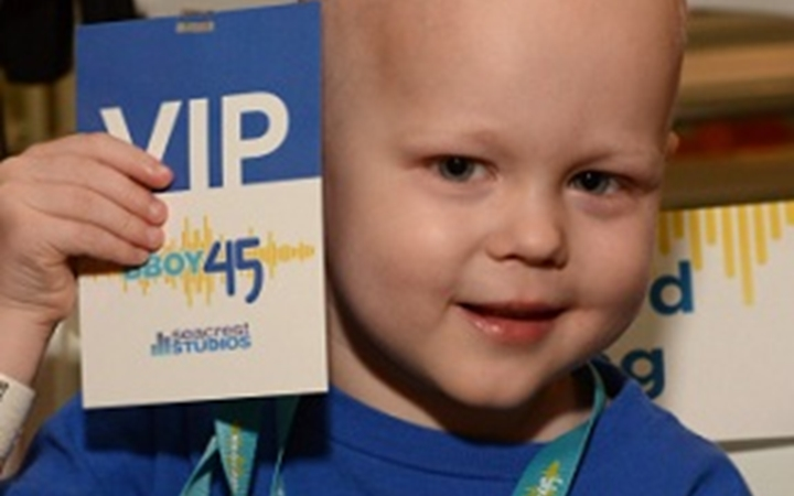 A young boy holds up his VIP pass to Seacrest Studios.