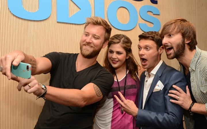 Ryan Seacrest poses for a group selfie at Seacrest Studios.