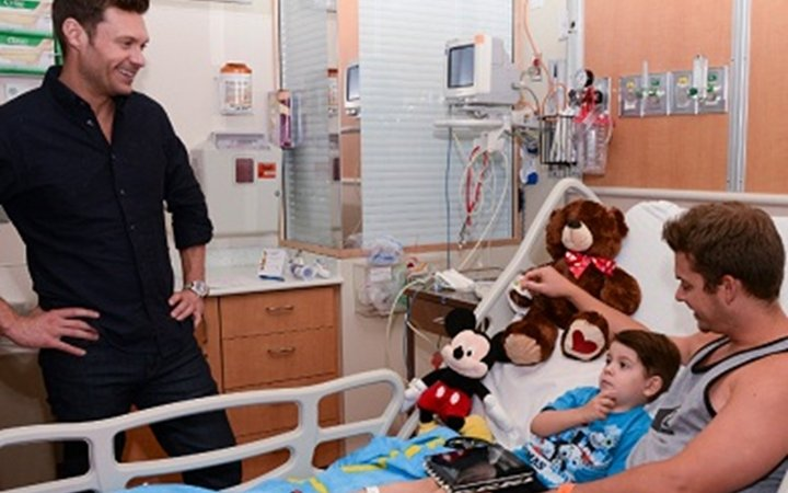 Ryan Seacrest visits a young boy in a hospital room at Children's Colorado.