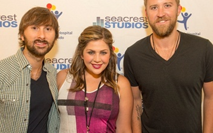 A popular band poses in front of the Seacrest Studios wall.