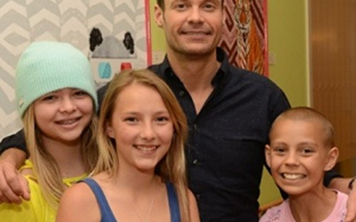 Ryan Seacrest poses with three girls at Children's Colorado.