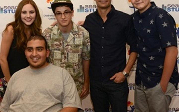Ryan Seacrest poses with four teenagers in front of the Seacrest Studios wall at Children's Colorado.