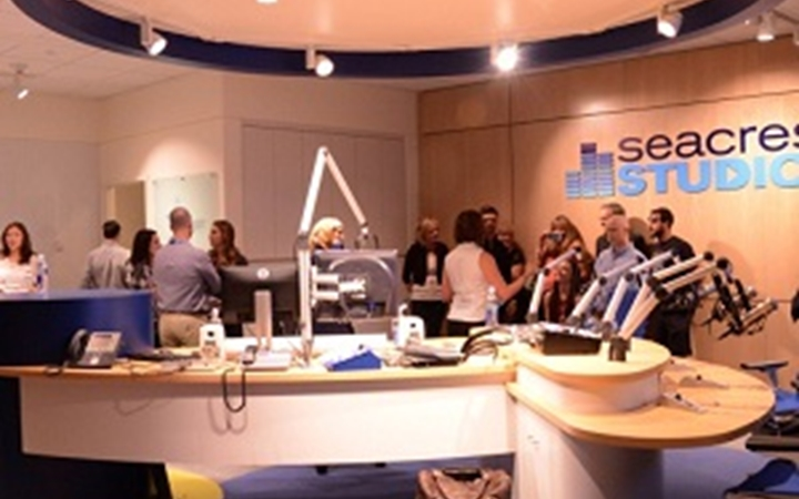 Several people get a tour of Seacrest Studios.