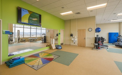 A picture of the sports gym at South Campus showing a stack of weights, balance ball, balance boards, a mirror and a TV hanging above the mirror on a bright green wall.