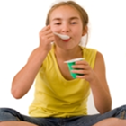 A young girl in a yellow tank top sits and eats yogurt for its vitamin D.