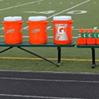 Gatorade and water bottles lined up on a football bench.