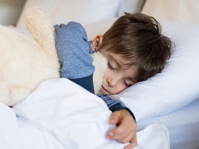 A young boy with brown hair and wearing blue pajamas hugs a stuffed rabbit while sleeping on a white pillow and under a white comforter.