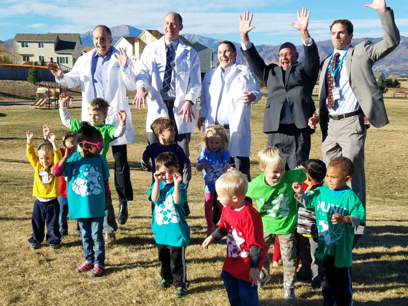 A group of doctors and kids stand in a mountain park cheering.