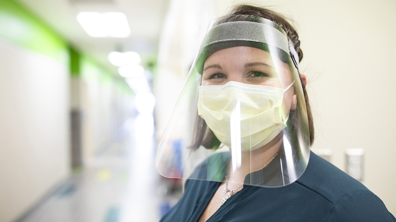 A nurse wearing a mask and face shield smiles at the camera.