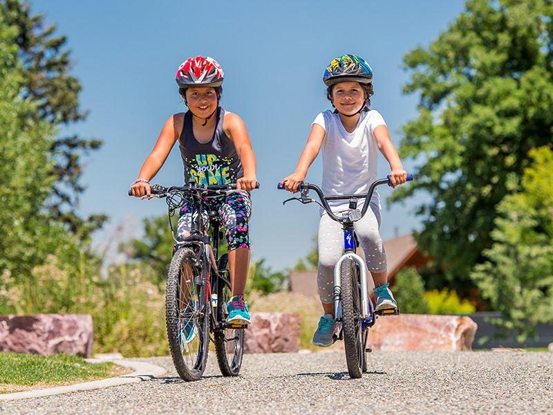 Two kids ride their bikes on a trail in a park in Colorado.