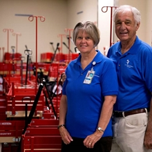 Two volunteers in bright blue polo shirts stand with the red wagons available at Children's Hospital Colorado.