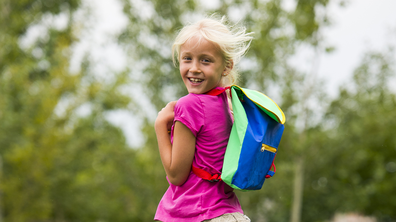 A girl with blonde hair and wearing a pink t-shirt and blue backpack stands in front of green trees.