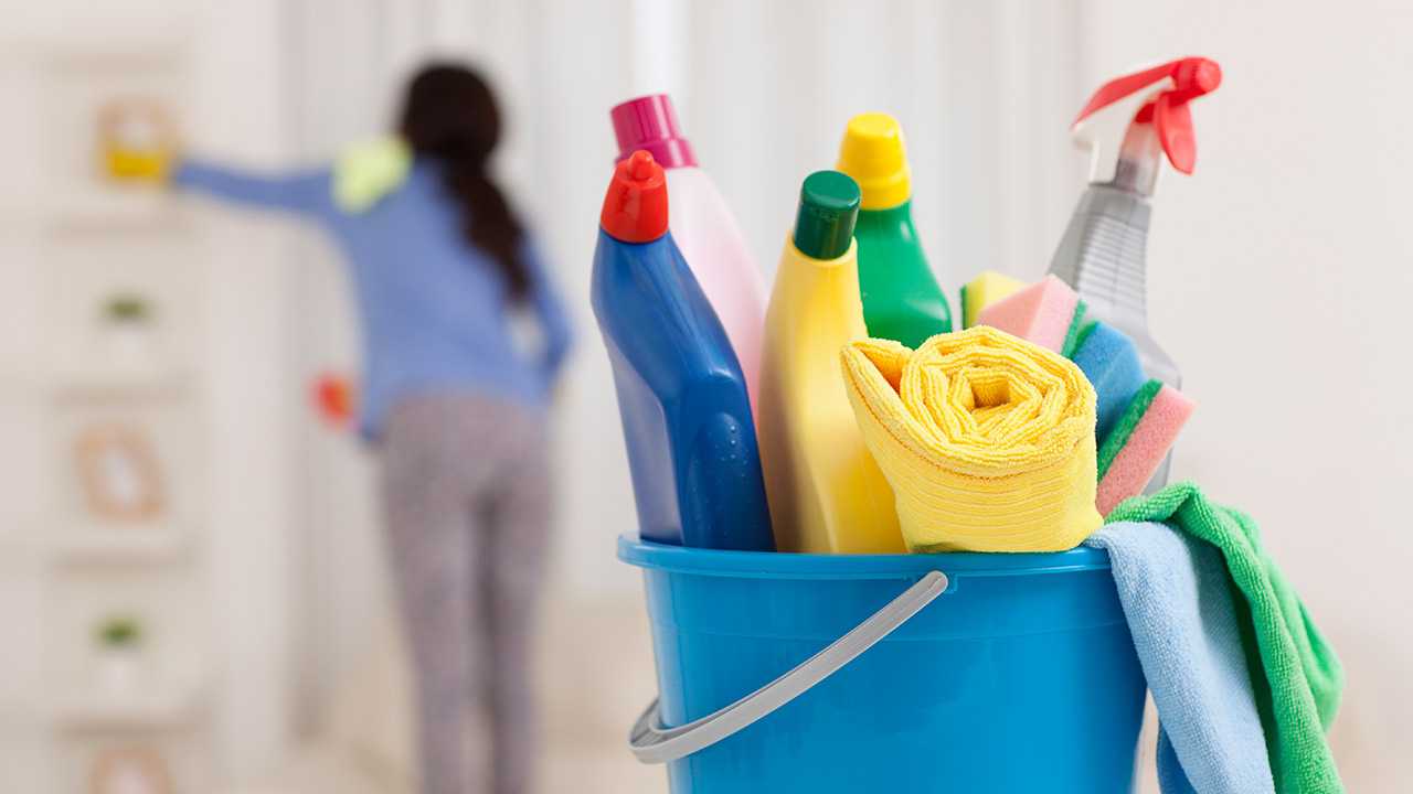 A closeup of a blue bucket holding multiple cleaning bottles and a yellow towel; and out of focus in the background is a woman with long dark hair and wearing a blue shirt while washing a wall.