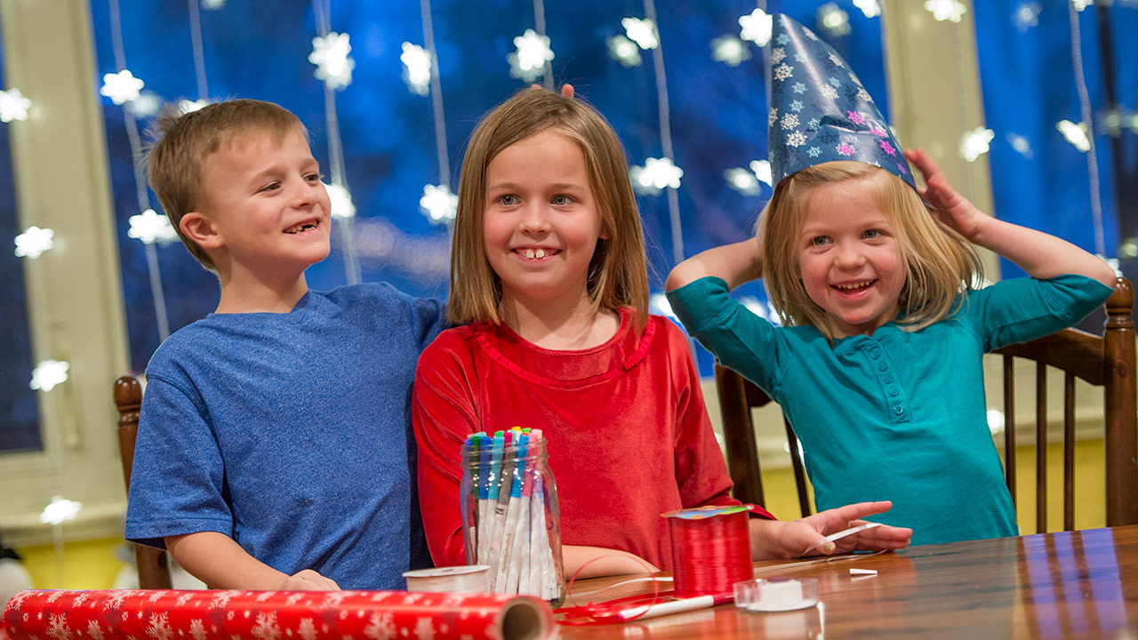 Three kids sit at a wood dining table with wrapping paper, ribbon and markers on it. The boy on the left is wearing a blue t-shirt, the girl in the middle is wearing a red shirt and the girl on the right is wearing a teal henley and holding wrapping paper on her head like a hat.