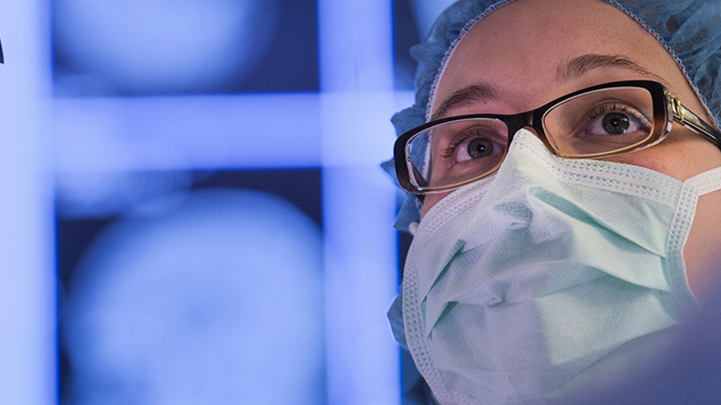 Close-up view of a doctor wearing glasses, a surgical head covering and surgical mask