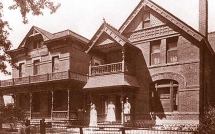 An old photo of the exterior of The Children's Hospital, which is a two level building with a fenced in porch and balcony; three women are standing at the entrance