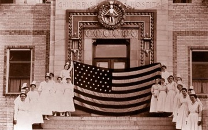 Nurses in white gowns and white hats stand on each side of the steps leading up to the hospital entrance and hold a giant American flag at the top of the stairs