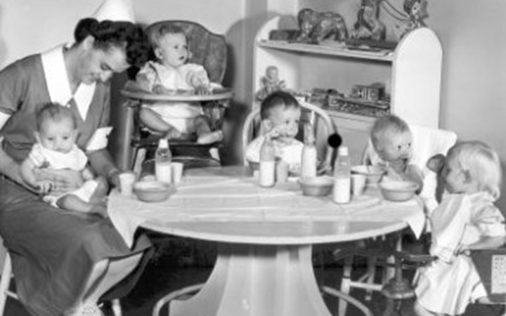 An old photo of a nurse wearing a dress and white hat holding a baby on her lap while another baby sits in a high chair and three toddlers sit around a table eating.