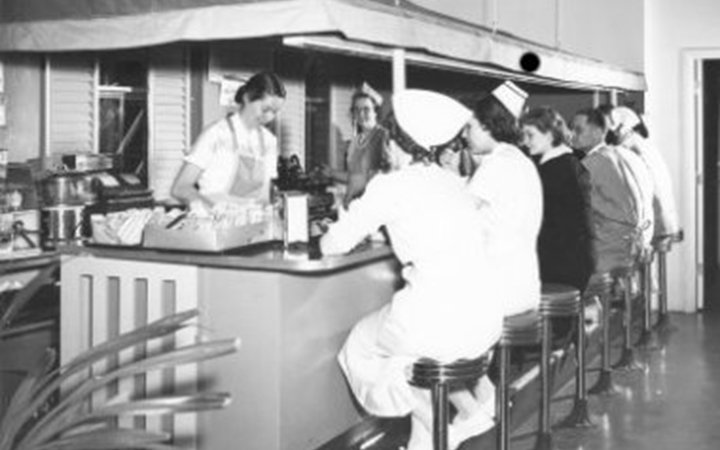A black and white photo of two women standing under an awning and behind a dining counter serve doctors and nurses who are sitting on stools at a snack bar.