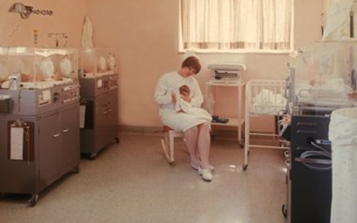 A nurse wearing a white dress and white hat sits in a rocking chair while holding a newborn baby. The room has newborn beds on each side and bright window on the back wall.