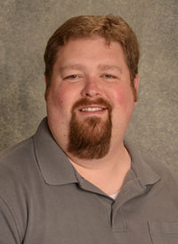 A headshot of heart perfusionist Cory Ellis who has light brown hair and a goatee and is wearing a gray polo.