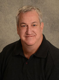 A headshot of heart chief perfusionist Scott Lawson who has short gray hair and is wearing a black polo.