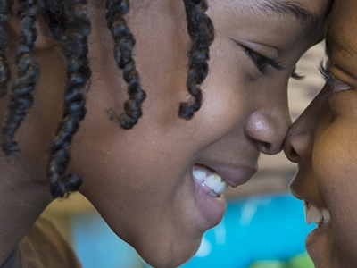 A close-up of two kids smiling and touching their foreheads and noses to each other.