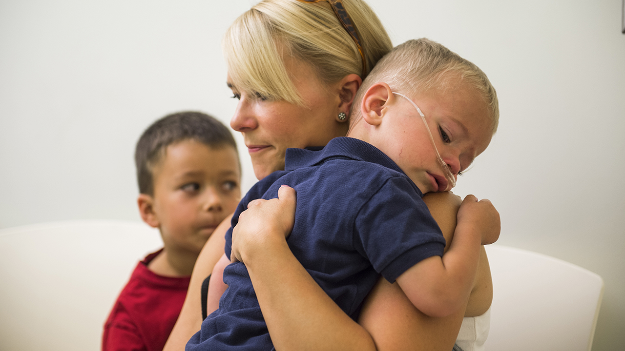 A mom holds her ill child while another boy sits next to her.