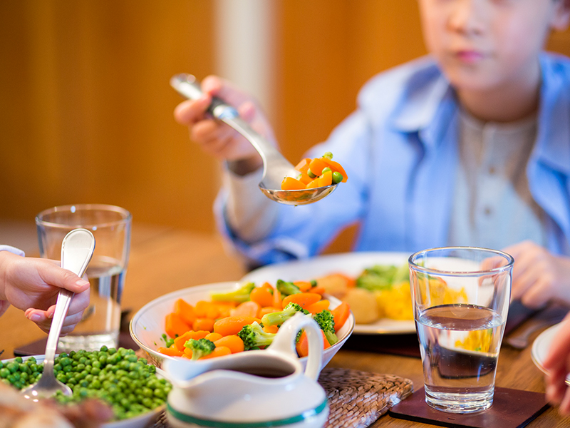 A boy wearing a blue button shirt over a gray henley sits at a wooden dinner table and holds cooked peas and carrots on his spoon over a bowl full of peas, carrots and broccoli. There is also a glass of water on the table.