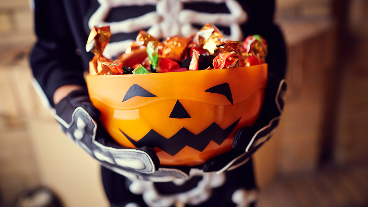 A close-up of a Halloween candy bowl that looks like an orange jack-o-lantern, being held by a kid in a skeleton costume.