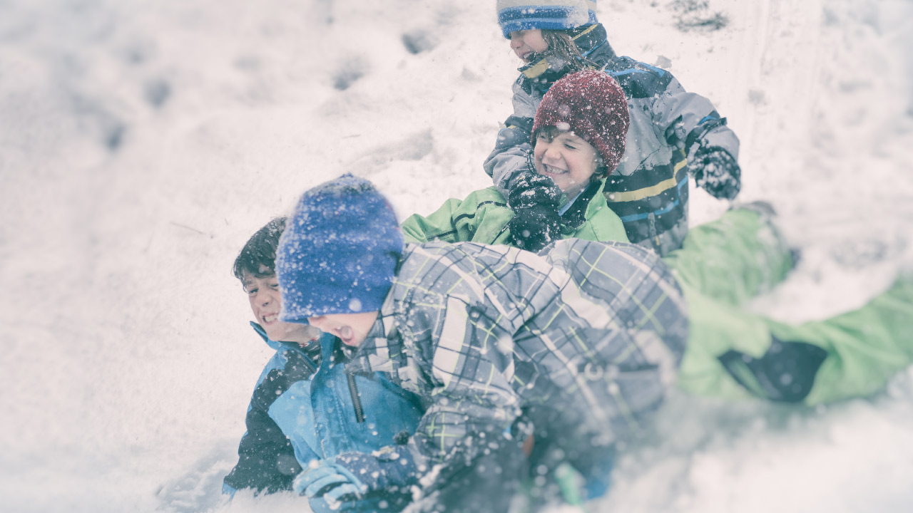 A group of four boys in blue and green snow gear wrestle in the snow.