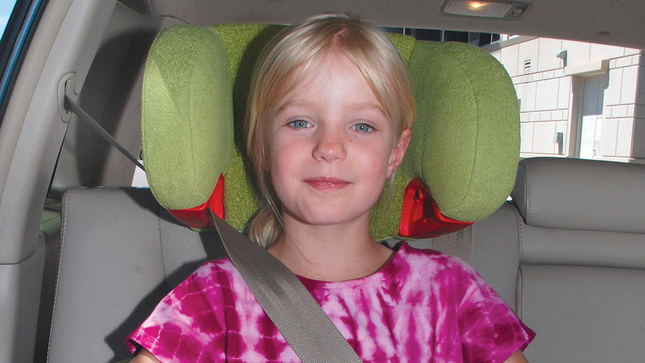 A girl with blonde hair in a ponytail sits in a lime green booster seat with a seatbelt across her shoulder inside a car with gray interior