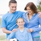 A family with a mom, dad and daughter wearing light blue and the girl holding a soccer ball.
