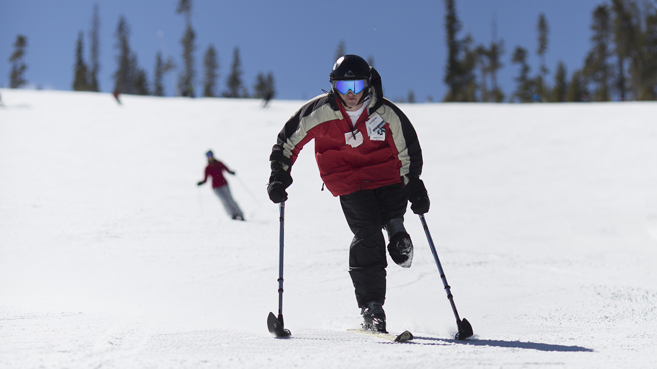 A teenager in the ARCH Program skis down the mountain using adaptive ski equipment.