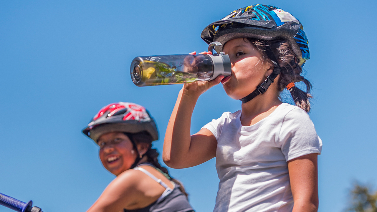 A girl wearing a bike helmet drinks water from a water bottle.