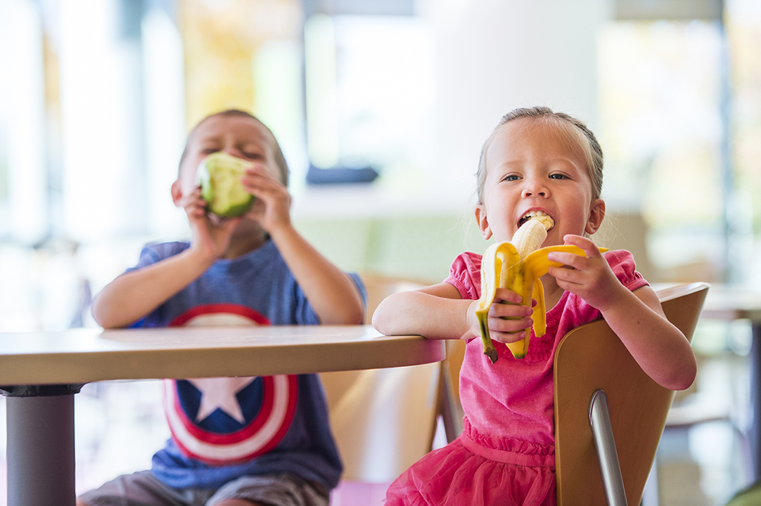 A girl in a pink dress sits at a light wood table eating a banana with a boy in a blue Captain America shirt, who is eating a green apple.