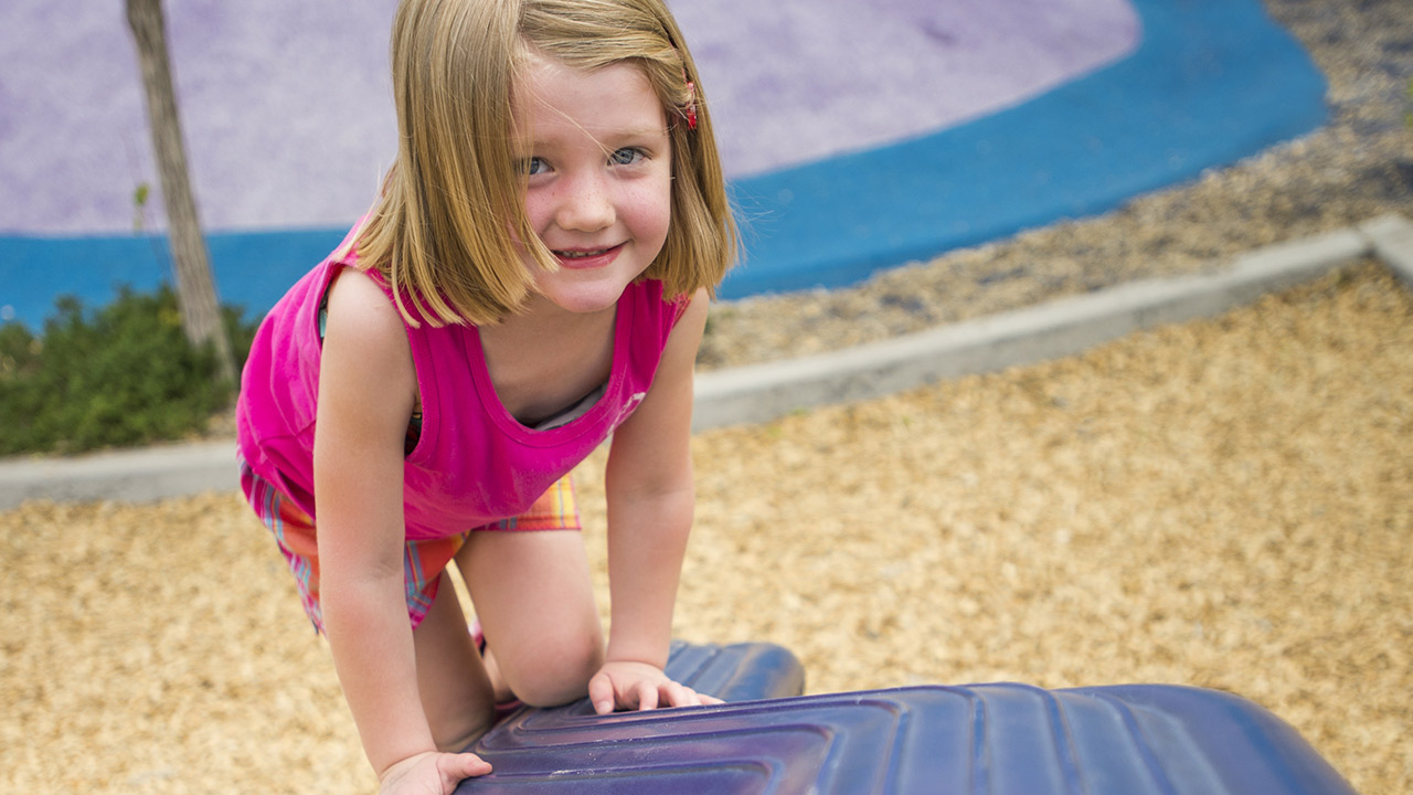 A girl wearing a pink tank top and plaid shorts kneels on a blue wobbly balance beam at the park playground that has wood chips on the ground.