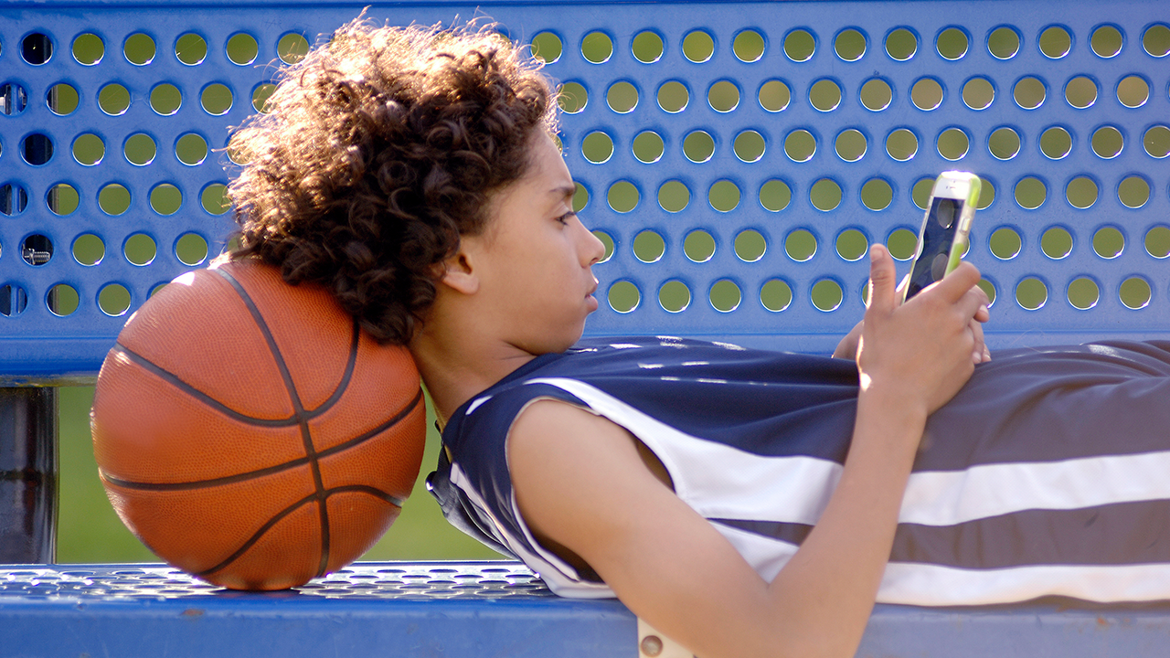 A kid lays on a bench with a basketball while using a cell phone.