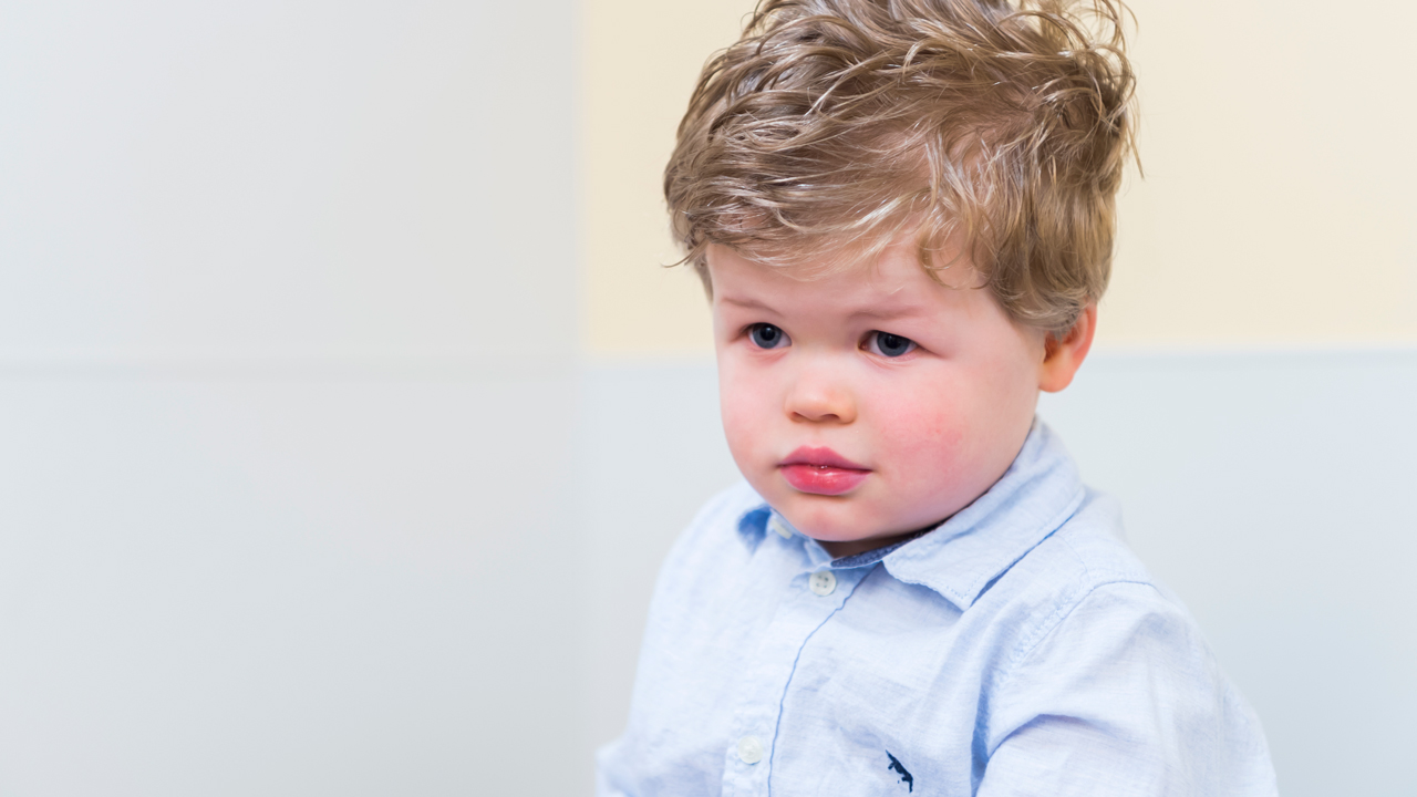 A toddler boy looks sad