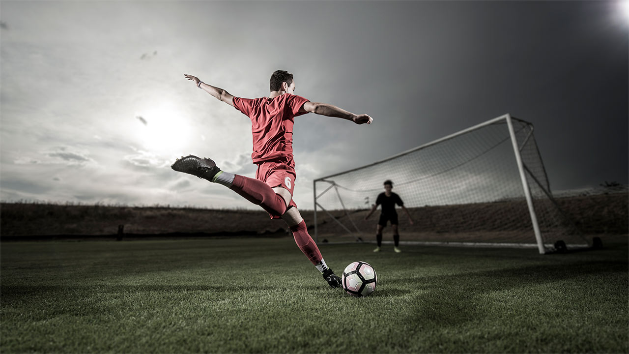 A soccer player starts to kick a ball toward the goal.