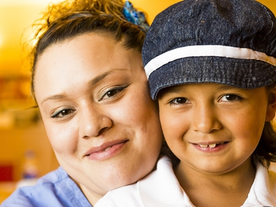 A nurse sits with a girl wearing a hat