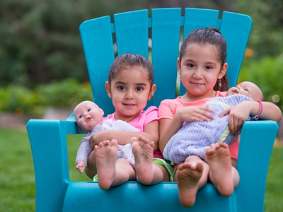 Two girls sit in a large blue chair holding baby dolls.