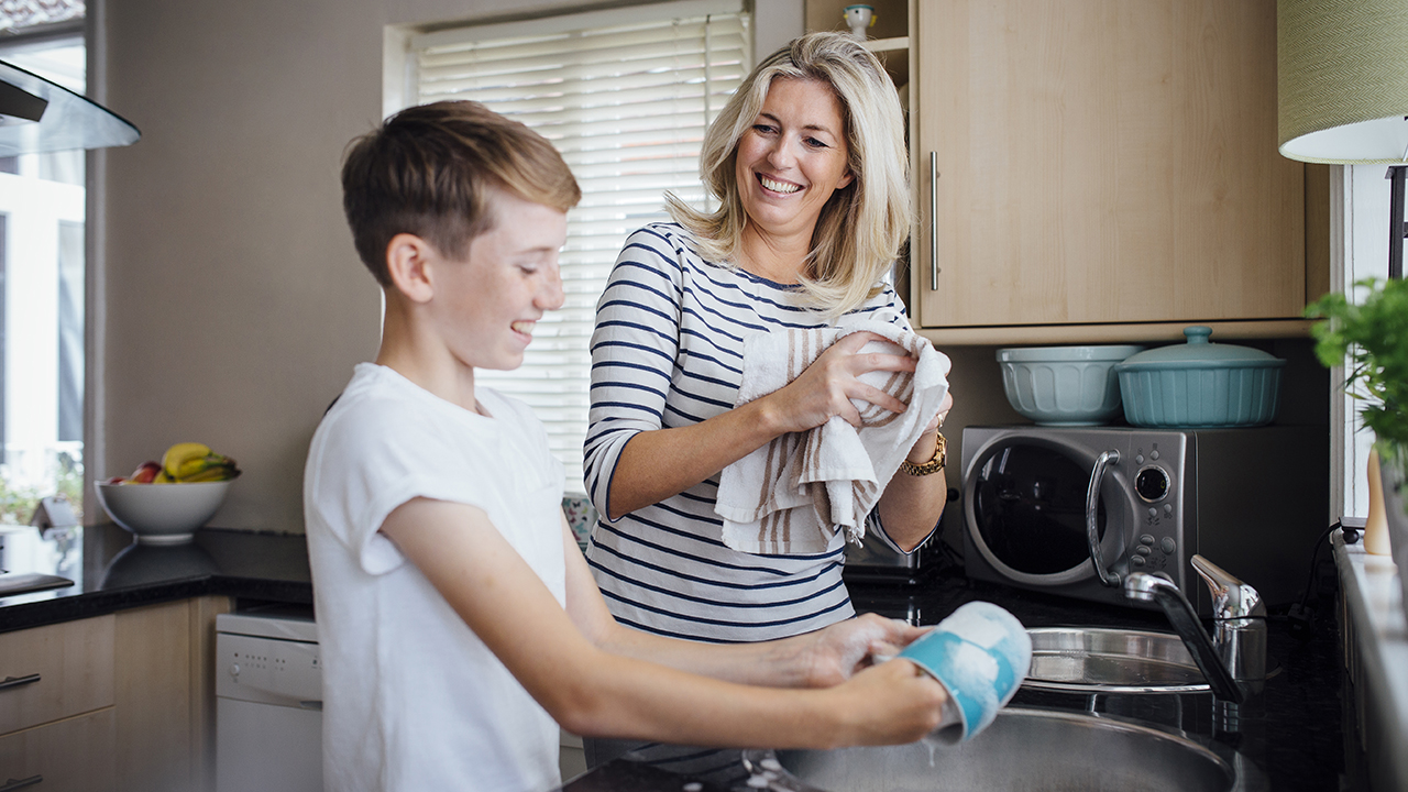 A child washes dishes with his mom